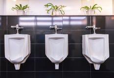 Drie witte urinoirs in mensenbadkamers Stock Foto's