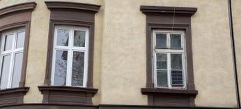 Drie witte vensters op de beige voorgevel van het huis Stock Afbeeldingen