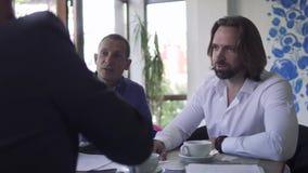 Drie zakenlieden maken een succesvolle overeenkomst bij restaurant stock videobeelden