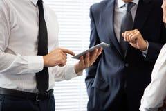 Drie zakenlui die en digitale tablet spreken gebruiken Royalty-vrije Stock Foto