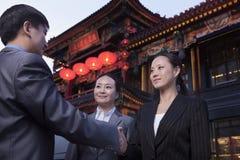 Drie zakenlui die in openlucht Chinese architectuur op achtergrond samenkomen. stock fotografie