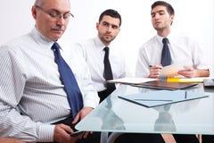 Drie zakenmanzitting bij lijst tijdens vergadering Stock Foto