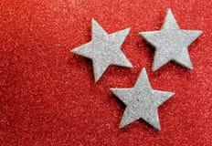 Drie zilveren sterren op heldere rode glittery verlichte achtergrond Stock Foto