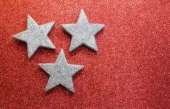 Drie zilveren sterren op heldere rode glitterytextuur Royalty-vrije Stock Foto