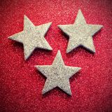 Drie zilveren sterren op rode glitterytextuur Royalty-vrije Stock Afbeeldingen