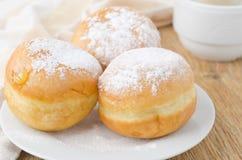 Drie zoete donuts die met gepoederde suiker wordt bestrooid Stock Foto's