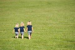 Drie zusters die op een gebied lopen Royalty-vrije Stock Afbeelding