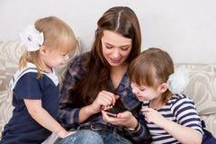 Drie zusters met smartphones Stock Foto