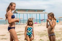 Drie zusters op het strand in het baden van bikinis stock afbeelding