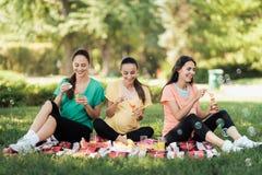 Drie zwangere vrouwen zitten in een park op een van de picknickdeken en slag bellen Royalty-vrije Stock Foto's