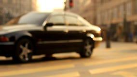 Drie zwarte auto's drijven onderaan de straat op de langzame die motiewijze, door mensen in stad bij zonsondergang wordt bevolkt stock video