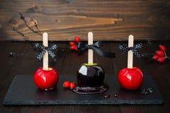 Drie zwarte en rode appelen van de vergiftkaramel Traditioneel dessertrecept voor Halloween-partij Royalty-vrije Stock Fotografie