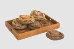 Dried abalone on bamboo tray in white background Royalty Free Stock Image