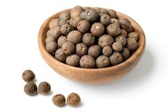 Dried allspice in the wooden plate, isolated on white background. Dried allspice isolated on the white background royalty free stock image