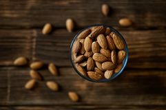 Dried almond nuts in a glass on a plank rustic background. Country style. Volume and shallow depth of field stock image