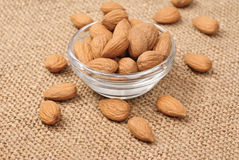 Dried almonds on glass bowl on canvas Royalty Free Stock Photo