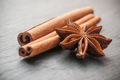 Dried anise and cinnamon on chalkboard background Stock Photo