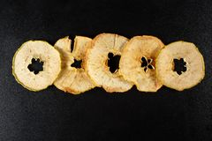 Dried apple slices on black background Royalty Free Stock Images