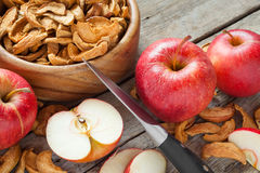 Dried apple slices and fresh apple fruit on table Stock Images