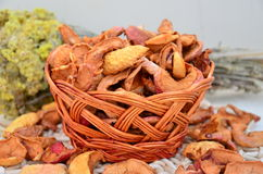 Dried apples in a basket. Bright dried apples in a wicker basket on the background of a bouquet of dried herbs Royalty Free Stock Image