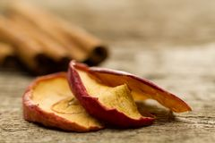 Dried apples with cinnamon sticks on old wooden background Stock Photography