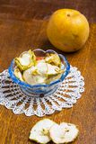Dried apples in glass bowl on wooden table Stock Image