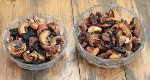 Dried Fruits in two round Bowls on a brown Background stock photos