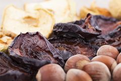 Dried plums on textile backgroundDried apples, plums and hazelnut on the table Royalty Free Stock Photos