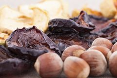 Dried plums on textile backgroundDried apples, plums and hazelnut on the table Stock Images