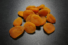 Dried apricots on black shiny background Royalty Free Stock Image