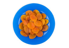 Dried apricots in blue glass plate isolated on white Stock Image