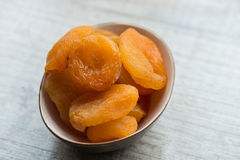 Dried apricots in brown plate on a white background. Close-up Royalty Free Stock Photography