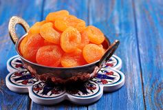 Dried apricots in a copper bowl on a blue background Stock Photos