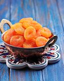 Dried apricots in a copper bowl on a blue background Royalty Free Stock Photography