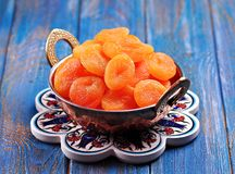 Dried apricots in a copper bowl on a blue background Royalty Free Stock Photos