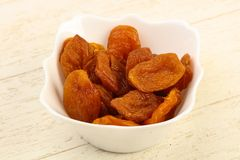 Dried apricots. Heap in the bowl over wooden background stock images