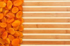 Dried apricots lying on a bamboo mat Stock Images