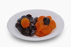 Dried apricots and prunes on a white background. Royalty Free Stock Photo