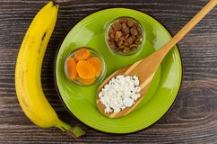Dried apricots, raisins, cottage cheese in spoon on plate, banan Stock Photos