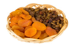 Dried apricots and raisins in wicker basket isolated on white Stock Photo