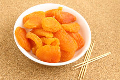 Dried apricots with toothpick. On the cork board Royalty Free Stock Photo