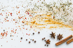 Dried aromatic spices and herbs scattered on grey Royalty Free Stock Photos