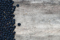 Dried aronia berries on wooden background. Healthy organic sun dried aronia berries on an old wooden background Stock Photography