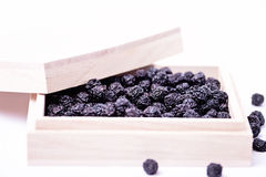 Dried aronia in a wooden box Stock Photo