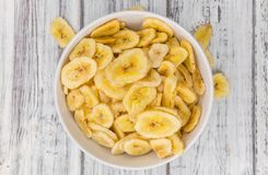 Dried Banana Chips on wooden background; selective focus royalty free stock photos