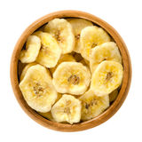 Dried banana chips in wooden bowl over white Royalty Free Stock Images
