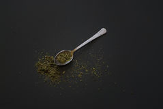 Dried basil on metal teaspoon on dark wooden table Royalty Free Stock Images