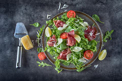 Dried beef bresaola. Salad bresaola arugula baby spinach tomatoes lime and cheese parmesan Royalty Free Stock Photos