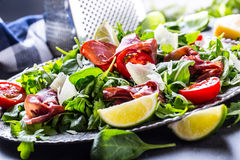 Dried beef bresaola. Salad bresaola arugula baby spinach tomatoes lime and cheese parmesan Stock Photo