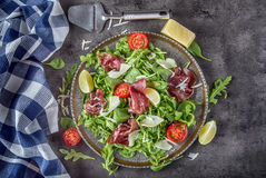 Dried beef bresaola. Salad bresaola arugula baby spinach tomatoes lime and cheese parmesan Royalty Free Stock Images
